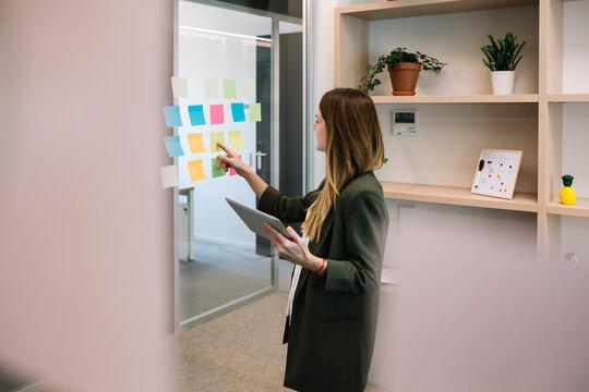 Female entrepreneur brainstorming while holding digital tablet at office