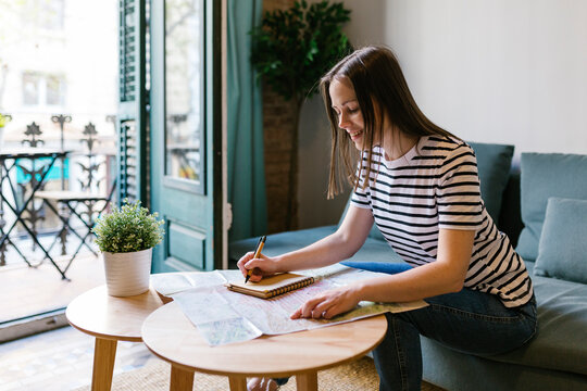 Smiling woman writing note on diary while sitting at table in apartment