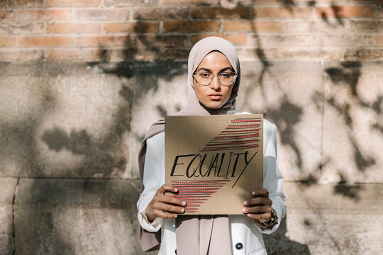 Young woman holding placard with equality text in front of wall on sunny day