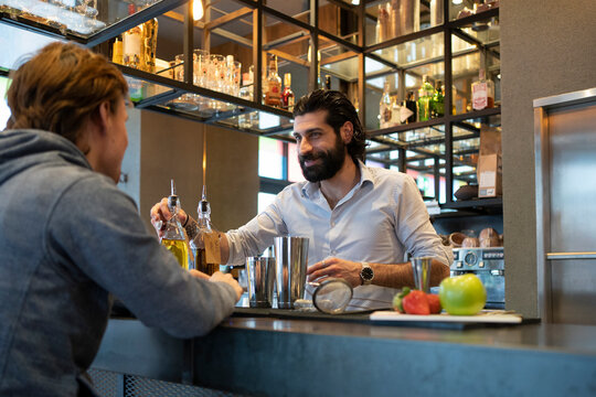 Smiling bartender serving alcohol to customer at bar counter