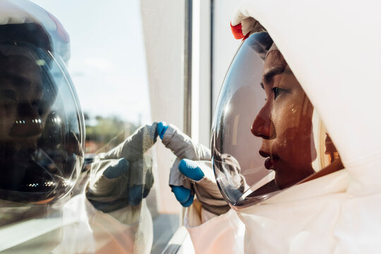 Young female astronaut in space helmet touching glass window