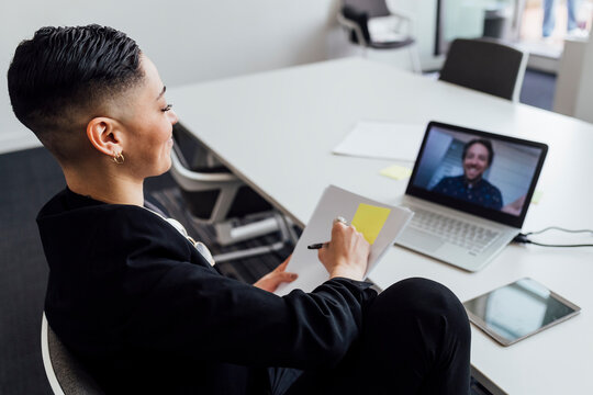 Female entrepreneur planning business strategy through video call on laptop at office