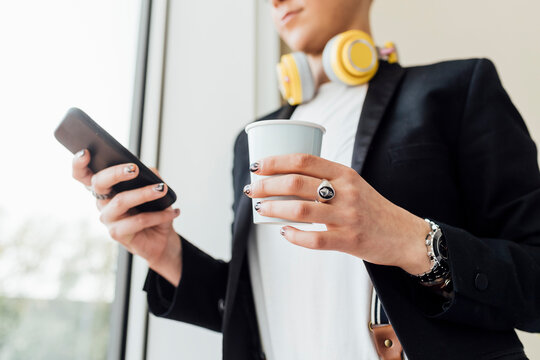 Businesswoman holding coffee cup while using mobile phone in office