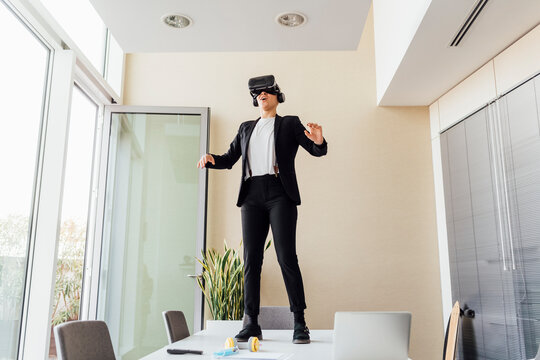 Young businesswoman using virtual reality simulator while standing on desk in office