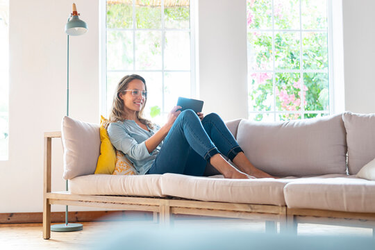 Smiling woman with eyeglasses holding digital tablet on couch in living room