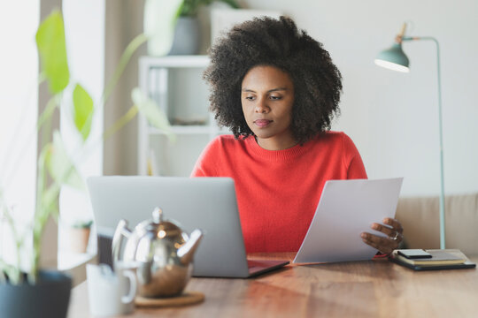 Curly hair woman with paper working on laptop at home
