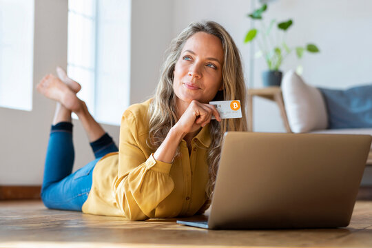 Contemplating woman with cryptocurrency credit card looking away while lying down in front of laptop at home