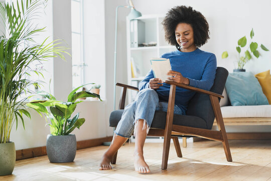 Smiling woman reading book while sitting on armchair at home