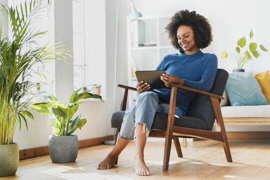 Young woman using digital tablet while sitting on armchair at home