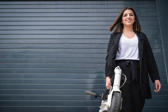 young business girl with her electric scooter, bilbao, spain