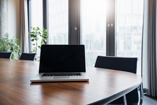 Laptop on table in board room at modern work place
