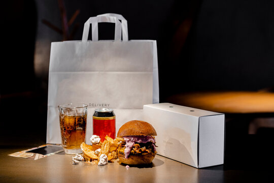 Food and drink arranged by paper bag and box on kitchen island