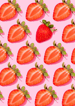 Pattern of rows of fresh halved strawberries lying against pink background