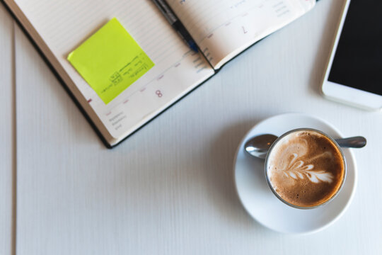 Coffee cup by mobile phone and diary on table