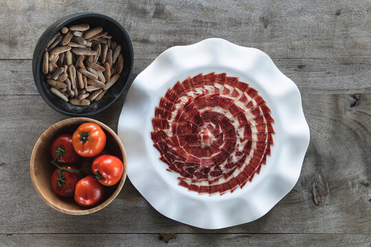 Tomatoes and slices of red meat on table