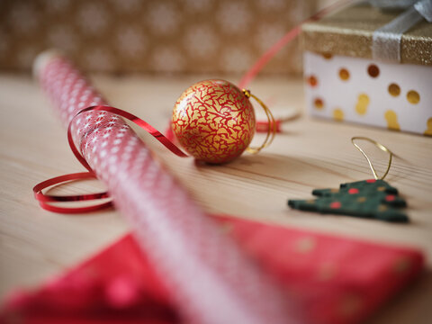 Gift wrapping paper with ribbon and Christmas decoration on table