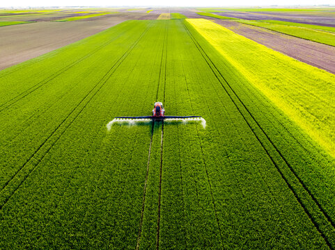 Tractor spraying pesticide on agricultural field