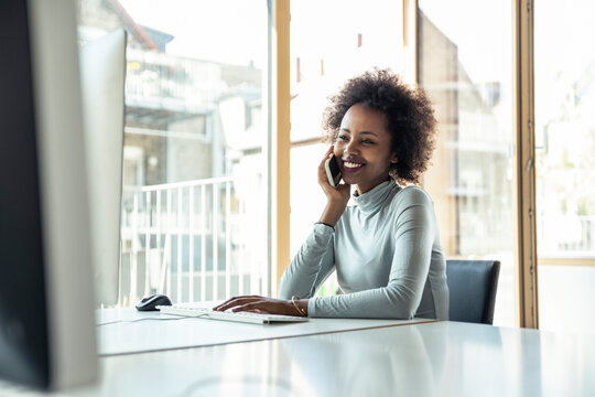 Smiling female professional talking on smart phone in office