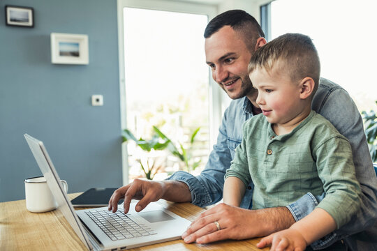 Smiling male freelancer using laptop while sitting with son at home