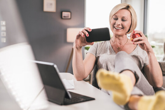 Smiling woman with apple watching movie on mobile phone at home