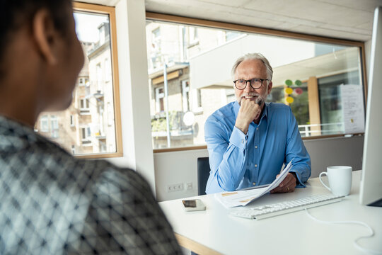 Smiling male professional with hand on chin discussing with female colleague in office
