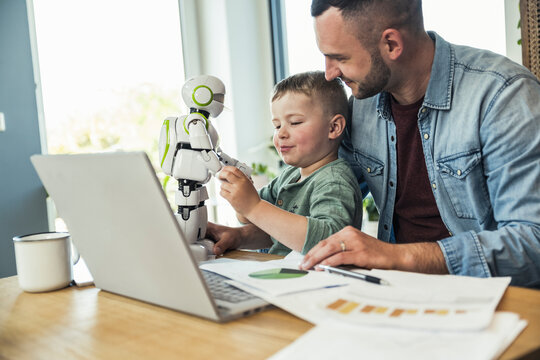 Smiling man looking at son playing with robot at home
