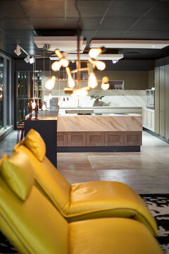 View to modern open plan kitchen with yellow leather chairs in the foreground