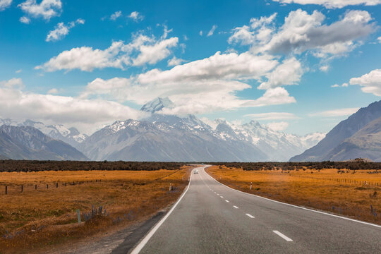 Clouds over asphalt highway stretching toward Southern Alps