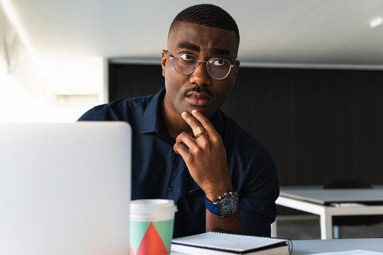 African American guy writing in notepad near laptop in office