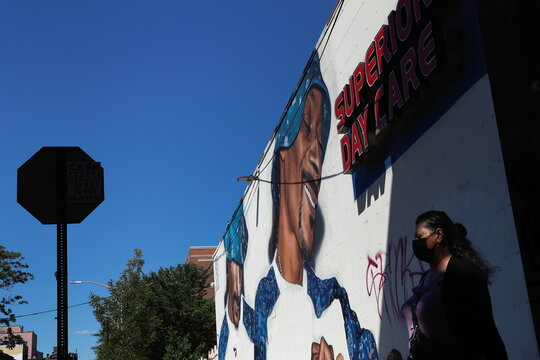 A woman wearing a protective face mask walks past a mural of entertainer Snoop Dogg in New York City