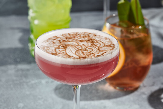 The Clover Club Cocktail is a cocktail consisting of gin, lemon juice, raspberry syrup, and egg white. Red Clover Club Cocktail with white foam and cinnamon powder. Vintage table