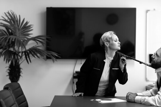 Black and white image of Businesswoman seduces office worker sitting at desk. Woman pulls a man for his tie. Seducing a subordinate in the office. seductive woman pulling tie of handsome man in suit
