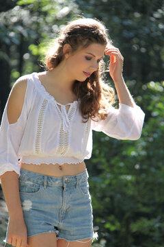 Junge Frau in weißer Bluse bei Sonnenlicht im Wald