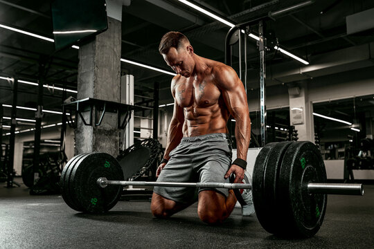Injury athlete with a barbell preparing for a workout in the gym for sports, fitness, weightlifting, sports injuries and people.