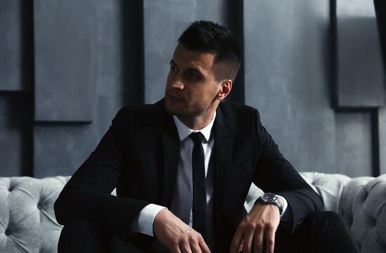 Handsome businessman on sofa indoors. Luxury lifestyle