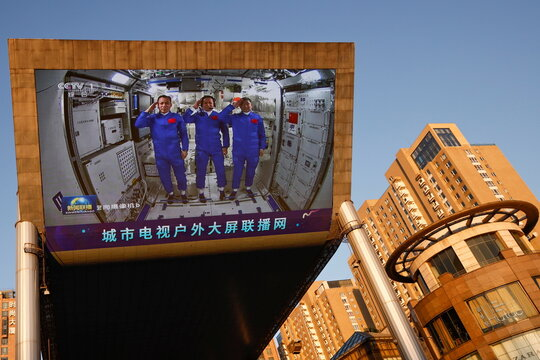 A giant screen shows Chinese astronauts of the Shenzhou-12 mission saluting insidetheTianhe core module of China's space station,at a shopping mall in Beijing
