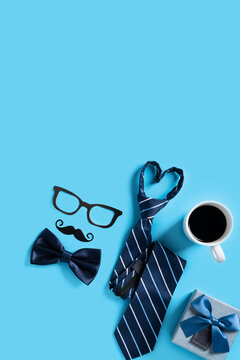 Father's day gift design concept. Top view of paper decoration with necktie and gift on blue table background.