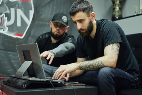 Male coworkers working on computer in tattoo salon
