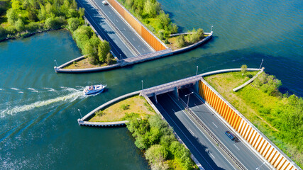 Aquaduct Veluwemeer, Nederland. Aerial view from the drone. A sailboat sails through the aqueduct on the lake above the highway.