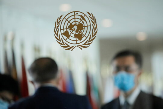 People wearing face masks are seen behind the emblem of the United Nations at its headquarters as U.N. General Assembly appointed U.N. Secretary-General Guterres for a second five-year term from January 1, 2022, in New York City