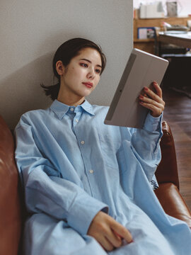 ソファでタブレットを手に持つ女性