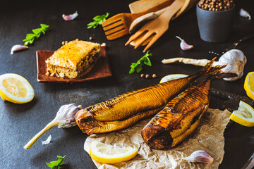 Fototapeta Mackerel. Smoked mackerel with additions. Fish with spices. Smoked food on a dark background. obraz