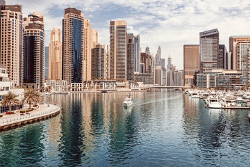 Fototapeta The boat sails along the canal in the Dubai Marina area against the backdrop of numerous residential skyscrapers and hotels obraz