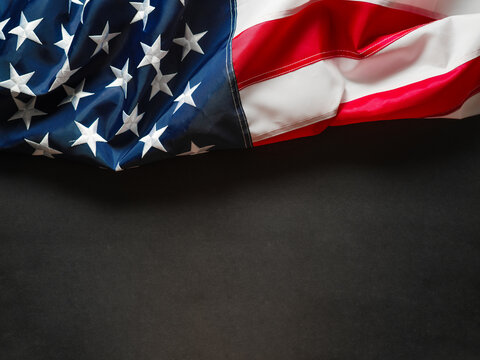 In the photo we see the American flag. A symbol of patriotism, national pride. Dark gray background. There is an empty space for your insert. There are no people in the photo.