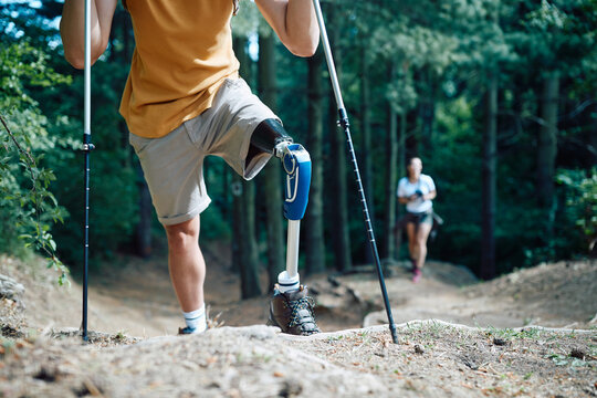 Unrecognizable hiker with prosthetic leg uses support sticks while walking through the woods.