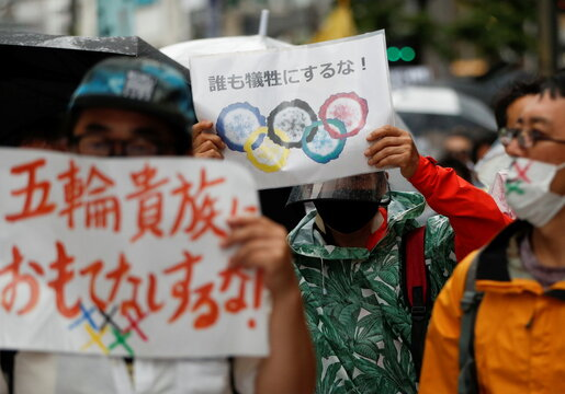 Anti-Olympics group's members hold placards during their protest march, in Tokyo