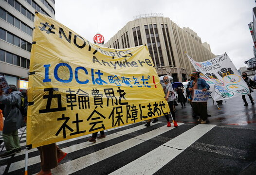 Anti-Olympics group's members display banners during their protest march, in Tokyo