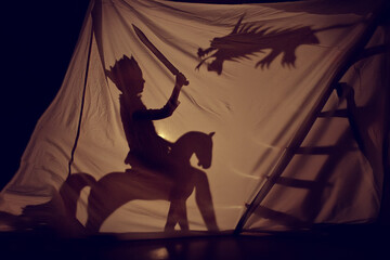 A fairy-tale shadow of a little prince on a horse with a sword and a dragon. Theatre. Childhood. Fairy tale.