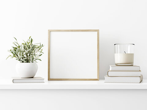 Square wooden frame mockup with green olive twigs and pile of books with candle on white wall background. 3d rendering, illustration