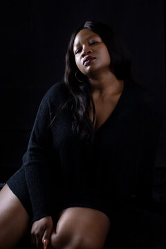 Beautiful happy black woman in a sultry pose  on a black background